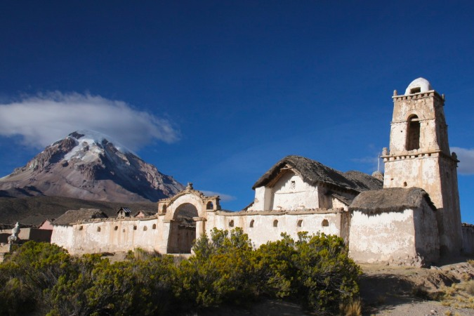 Adobe church with Vulcan Sajama, Altiplano, Bolivia