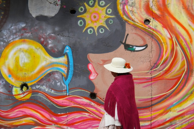 A woman walks past street art in La Paz, Bolivia