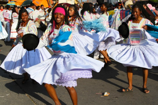 A dancer in the Virgen de Guadalupe festival smiles into the camera, Sucre, Bolivia