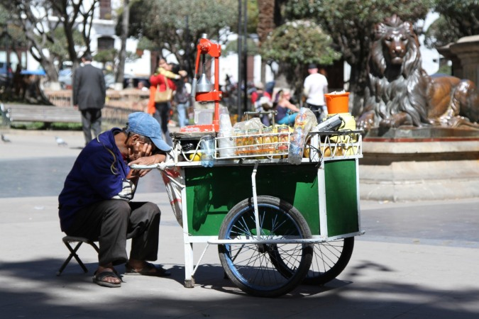 Orange juice vendor takes a nap, Plaza 25 de Mayo, Sucre, Bolivia
