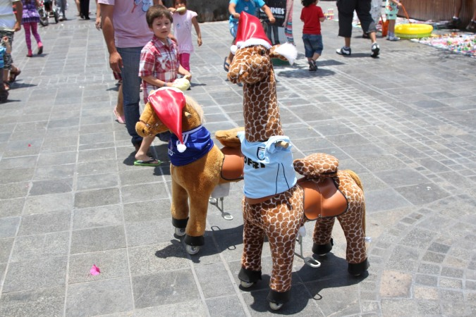 Toy animals ridden by children in the Plaza de Armas, Iquique, Chile