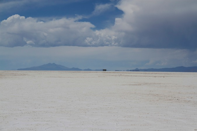 A bus speeds across the Salar de Uyuni, Bolivia