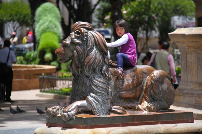 Young girl sits on lion, Plaza 25 de Mayo, Sucre, Bolivia