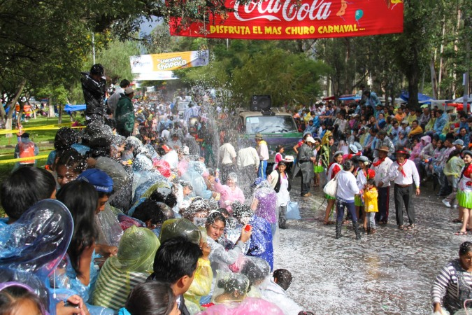 Part of the stand erupts with a foam fight, carneval, Tarija, Bolivia