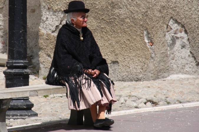 A woman sits outside a church in Plaza San Pedro, La Paz, Bolivia