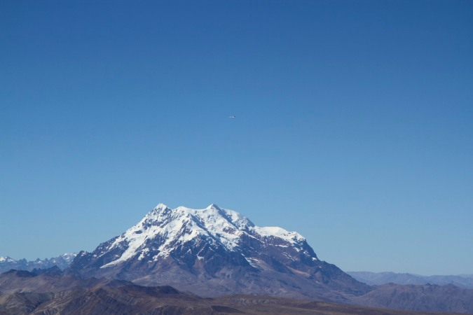 A plane, looking tiny and insignificant, flies over Illimani, Cordillera Real, Bolivia