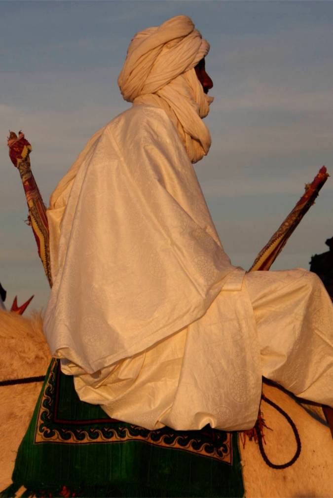 A Tuareg sits on his camel at sunset, Sahara Desert, Mali, Africa