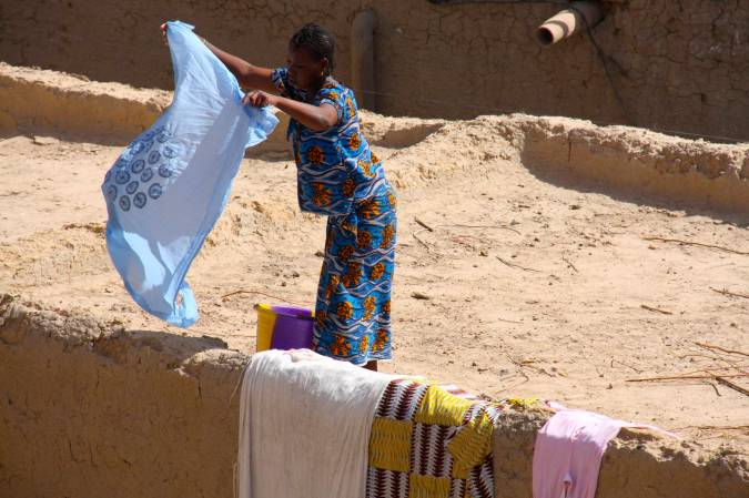 A woman dries clothes on a rooftop, Mopti, Mali, Africa