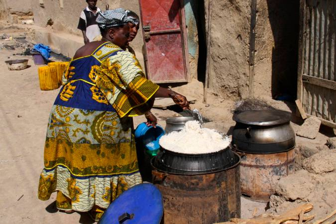 A woman cooks rice in the street, Mopti, Mali, Africa