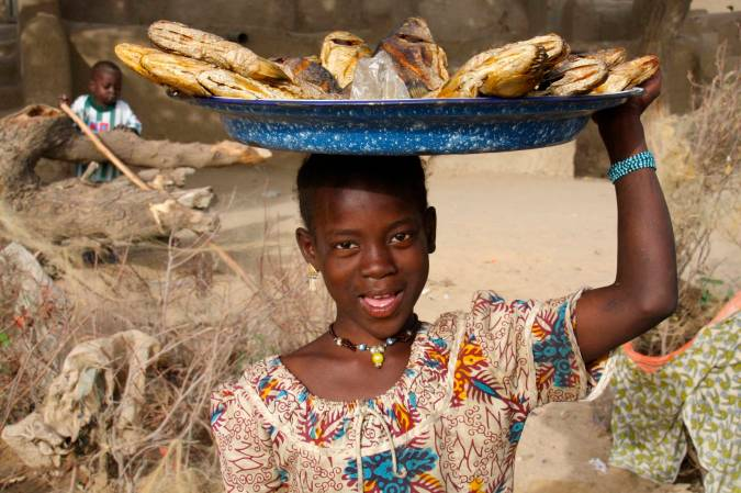 A young girl sells fish, Niger River, Mali, Africa