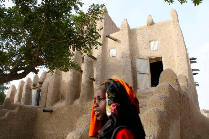 A girl passes by the village mosque, Niger River, Mali, Africa