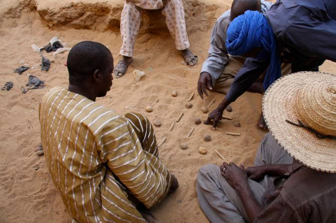 Men play 'tiddas', a game with sticks and stones, Niafunké, Mali, Africa