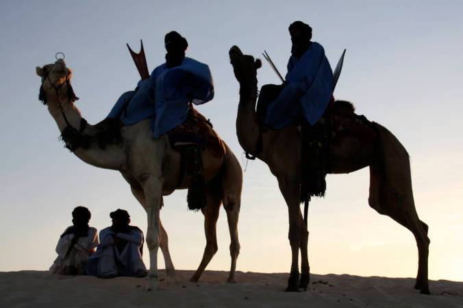 Tuareg and camels at sunset, Sahara Desert, Mali, Africa