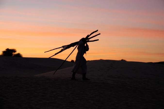 A man walks across he desert at sunset, Sahara Desert, Mali, Africa