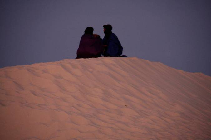 Two people sit in the desert at sunset, Sahara Desert, Mali, Africa