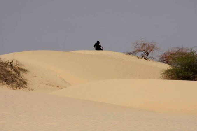 A man prays on a sand dune, Sahara Desert, Mali, Africa
