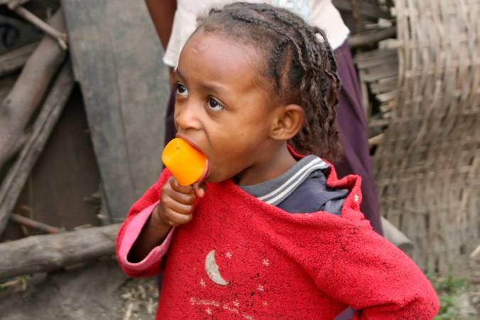 A young girl eats a ice lolly, Axum, Ethiopia, Africa