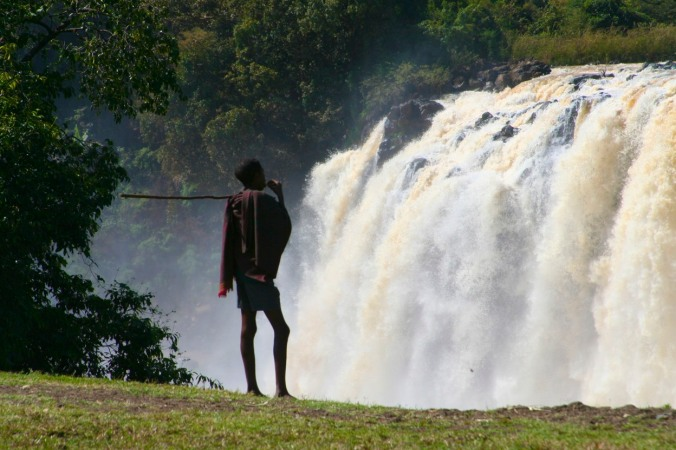 A young shepherd looks over the Blue Nile waterfalls, Bahir Dar, Ethiopia, Africa