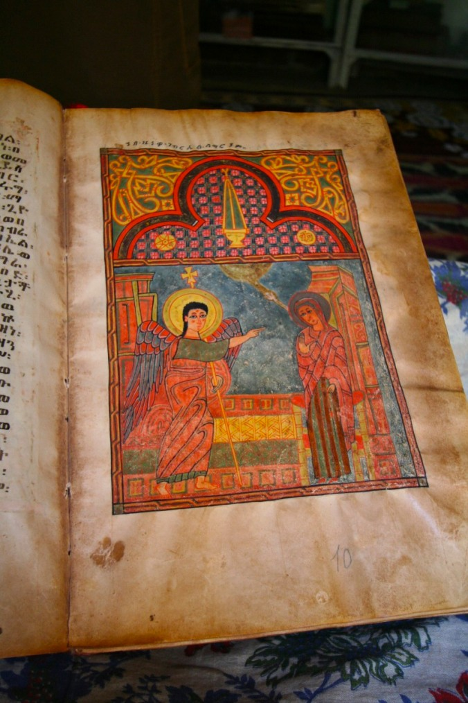 A priest shows an ancient illustrated manuscript, Kebran Gabriel Monastery, Lake Tana, Ethiopia, Africa