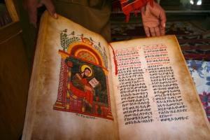 A priest shows an ancient illustrated manuscript, Kebran Gabriel Monastery, Lake Tana, Ethiopia, Africa