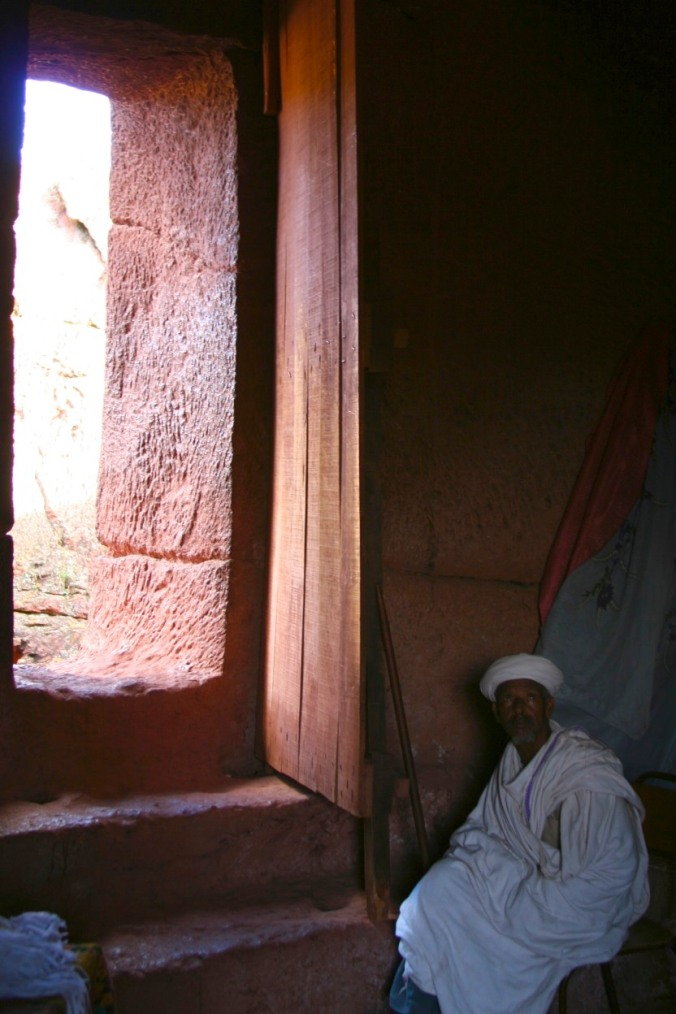 Priest sits by a doorway, Lalibela, Ethiopia, Africa