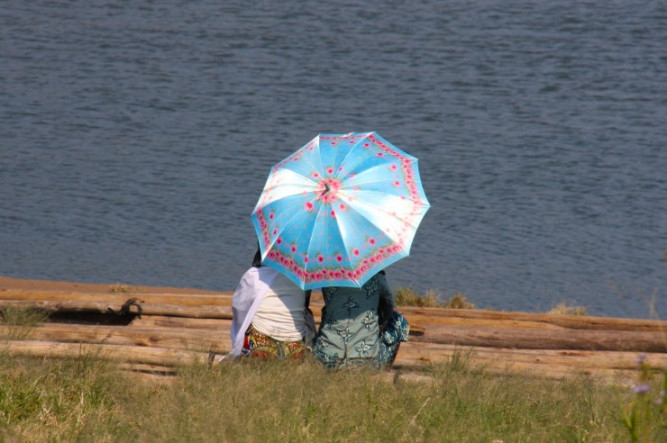 Women with an umbrella, Lake Kivu near Gisenyi, Rwanda, Africa