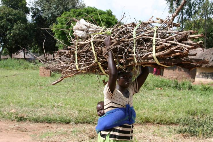 Woman carries wood and baby, Internal Displacement Camp, Gulu, Uganda, Africa