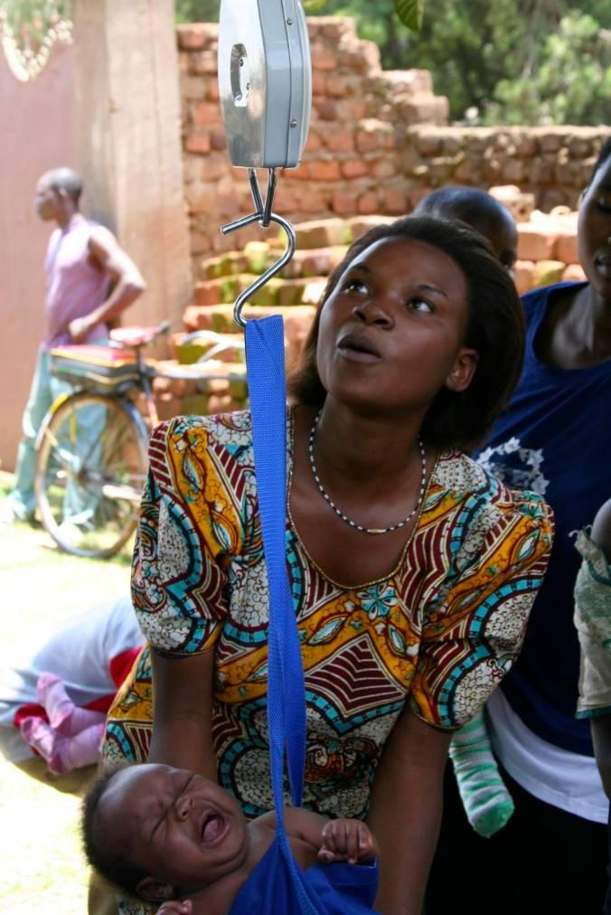 A woman weighs her baby, Iganga, Uganda, Africa