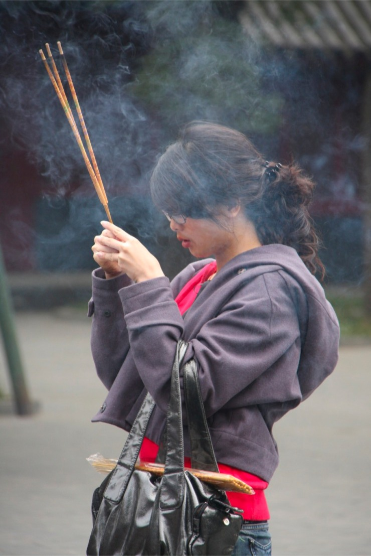 People pray and burn incense, Yonghe Gong Buddhist temple, Beijing, China