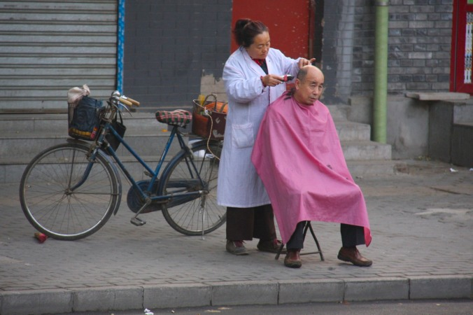 A man gets a haircut on the street, Beijing, China