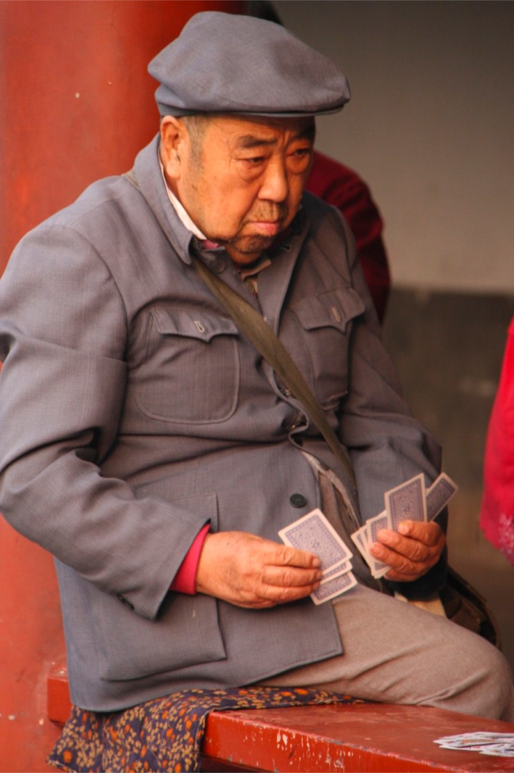 A man gets plays cards on the street, Beijing, China