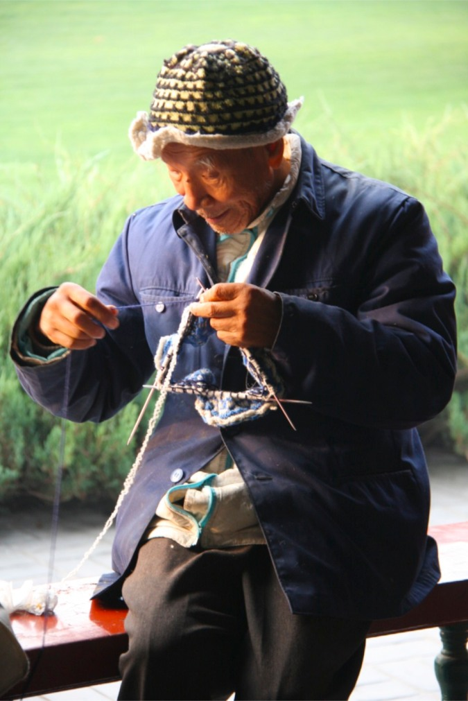 A man knits, the Temple of Heaven, Beijing, China