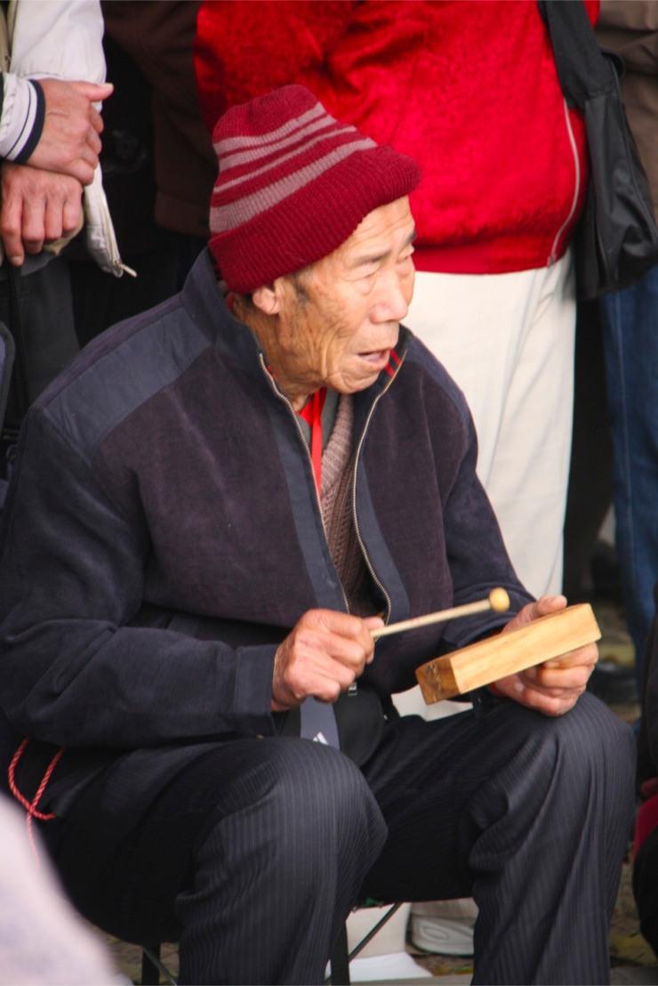 An old man plays a tiny instrument in Beihai Park, Beijing, China