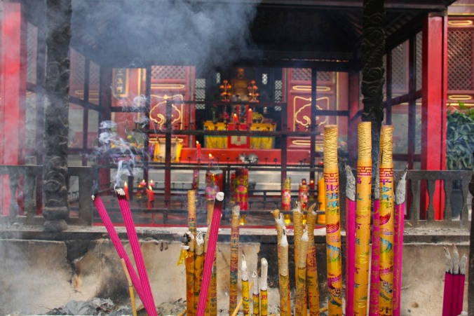 Incense burns at a temple shrine in a hutong, Beijing, China