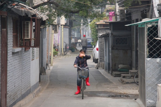 A woman cycles in a hutong, Beijing, China