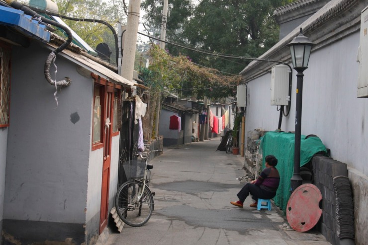 A woman sits in a hutong, Beijing, China