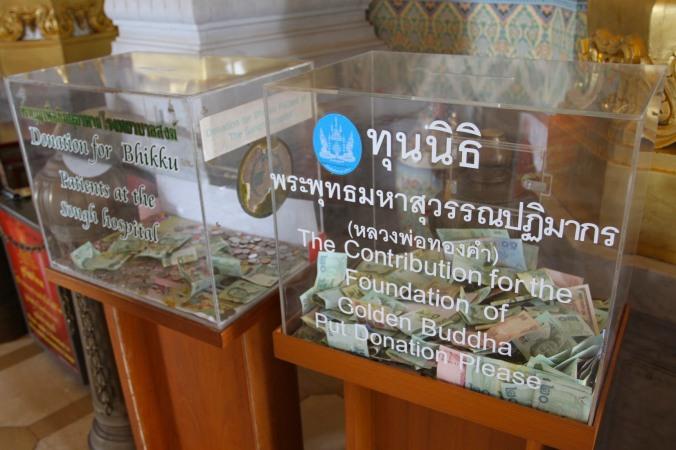 Donations at Wat Traimit, Bangkok, Thailand