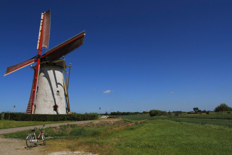 Cycling past a windmill in Zeeland, Netherlands