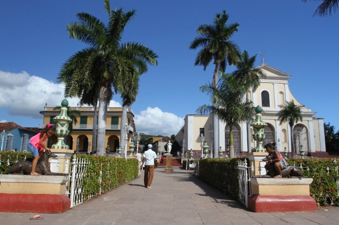 Children play on the statues in Plaza Major, Trinidad, Cuba