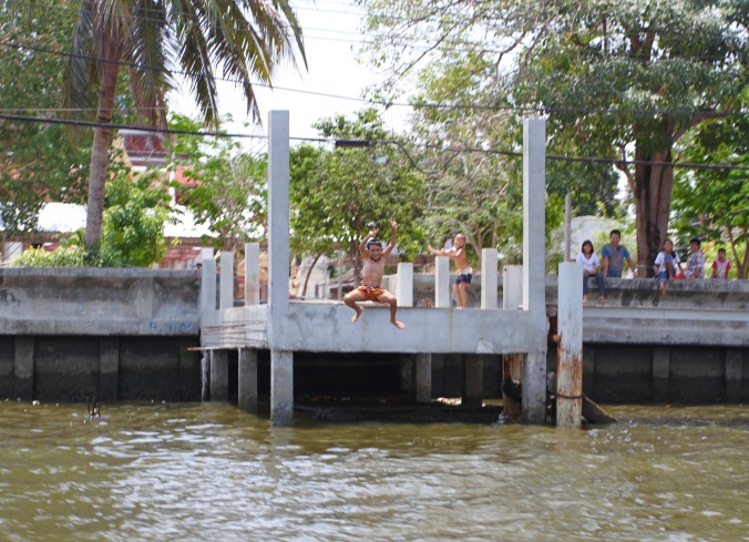 Children swimming in the canals of the Thonburi district of Bangkok, Thailand